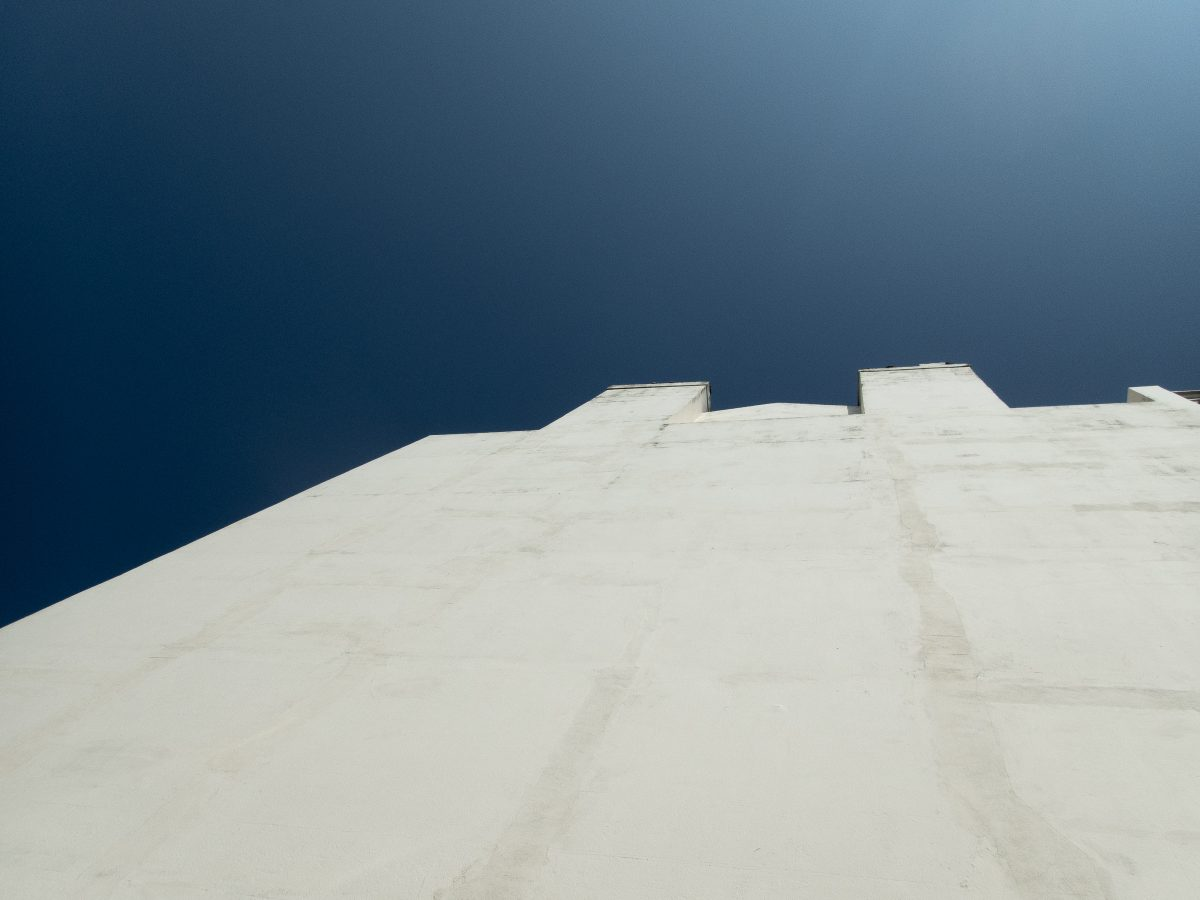 Photograph looking up at a white building with blue sky in the background
