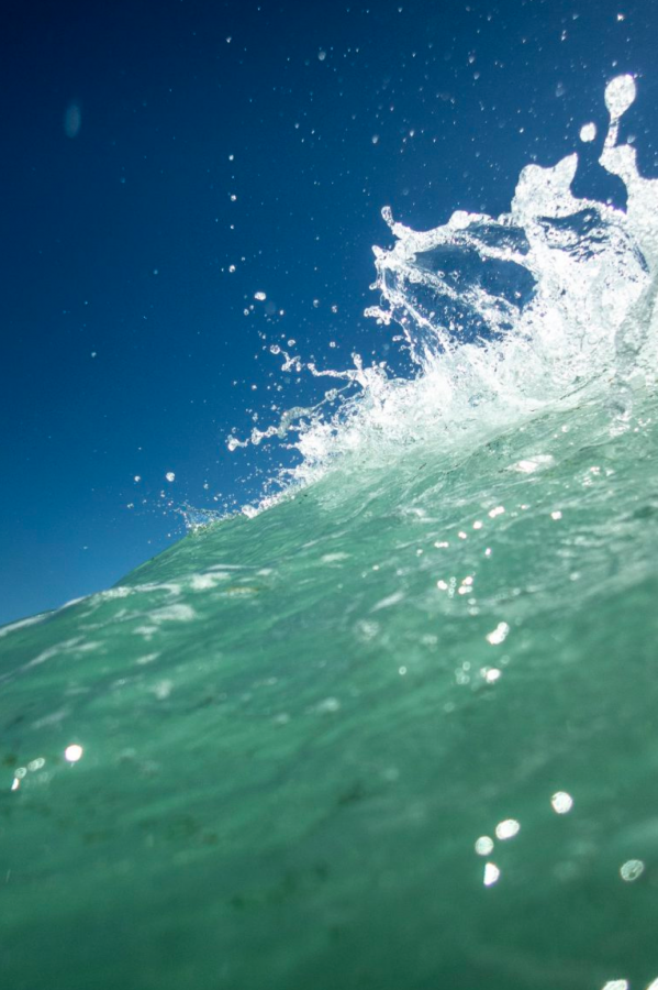 Photograph of a wave with blue sky in the background